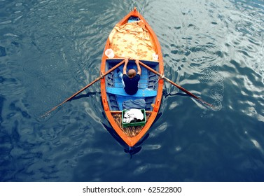Young man on a boat : rowing fisherman