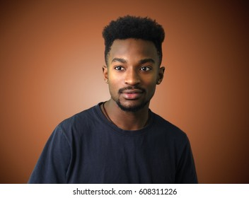 young man on brown background t-shirt studio portrait