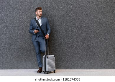 Young man on business trip walking with his luggage at airport.