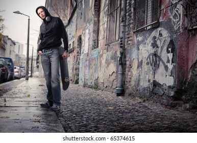 Young man on a city street holding a skateboard