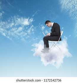 Young man on cloud working on laptop. Sky background. Communication and work concept