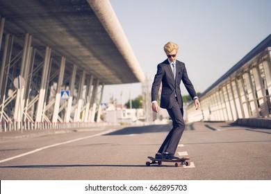 Young man on the fashion nice suit on the longboard skatebourd at the airport near modern building
