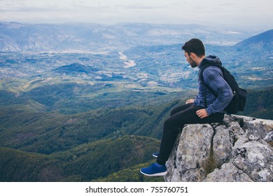 Young man on on high cliff. Mountain view.