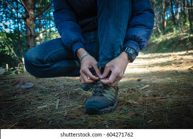 Young man on a hiking trail ties the shoelace on her walking shoe, closeup photo