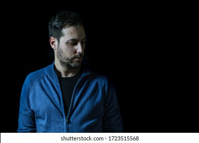 young man on his 40s with black background. Concept of sadness and loneliness