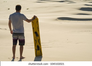 Young man on his back looking at the sand dunes, preparing to practice sandboarding.