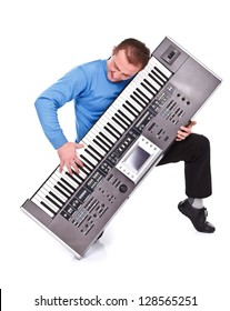 Young man on his knee playing on synthesizer over white background
