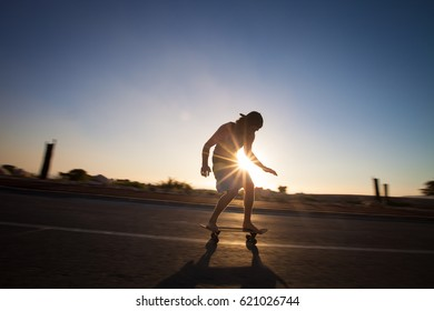 Young man on a longboard on empty road.