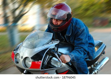 Young man on motorcycle (motorbike) with blurred background (motion blur).