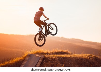 Young man on a mountain bike performing a dirt jump