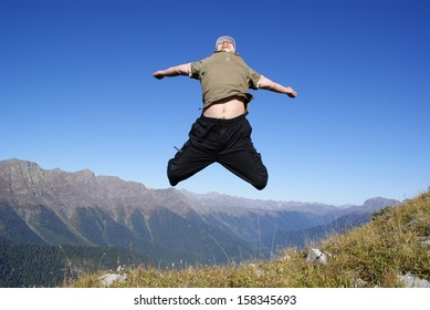 Young man on a mountain slope in the jump