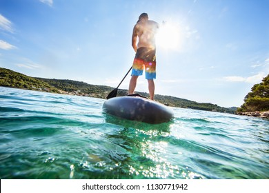 Young man on paddleboard, half under and half above water composition. Paddleboarding is the modern way of transportation and water activity sport.