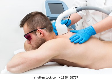 A young man on a procedure of laser hair removal in the salon of aesthetic beauty.