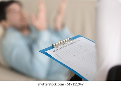 Young man on reception at the psychotherapist. Focus on clipboard with medical patient card in doctor hand. Filling personal information about new patient in clinic. Healthcare and treatment. Close up