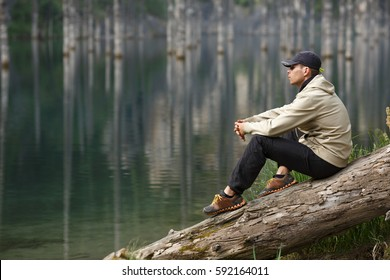 Young man on the shore of a mountain lake