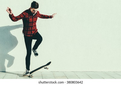 Young man on the skateboard on the city street