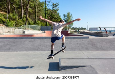 young man on skateboard jumping in skatepark