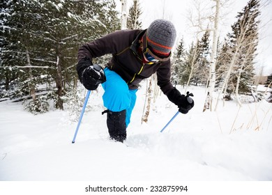 Young Man on Snowshoes Struggles to Get Up Snowbank