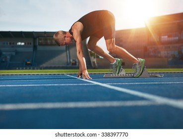 Young man on starting position ready for running. Male athlete in the starting blocks on sports track about to run.