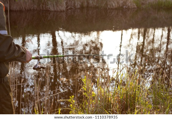A young man on a summer fishing with fishing rods and tackles fishing on the river