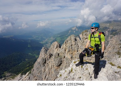 Young man on top of mountain admiring the view from the top of Piz da Cir Via ferrata climbing route in Puez Odle (Dolomites / Dolomiti mountains in Italy) on a sunny day of summer