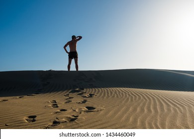 young man on top of sand desert dune looking to toward horizon in a symbolic way with clear blue sky