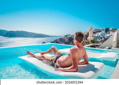 Young man on vacation at Santorini, Men at the swimming pool looking out over the Caldera ocean of Santorini, Boy at the infinity pool Oia Santorini Greece
