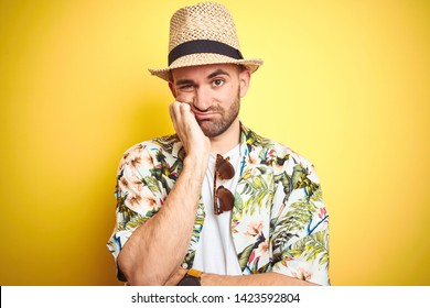 Young man on vacation wearing hawaiian flowers shirt and summer hat over yellow background thinking looking tired and bored with depression problems with crossed arms.
