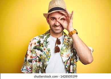 Young man on vacation wearing hawaiian flowers shirt and summer hat over yellow background doing ok gesture with hand smiling, eye looking through fingers with happy face.