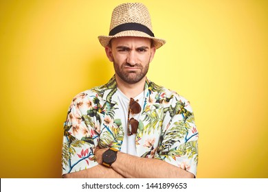 Young man on vacation wearing hawaiian flowers shirt and summer hat over yellow background skeptic and nervous, disapproving expression on face with crossed arms. Negative person.