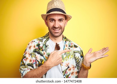 Young man on vacation wearing hawaiian flowers shirt and summer hat over yellow background amazed and smiling to the camera while presenting with hand and pointing with finger.