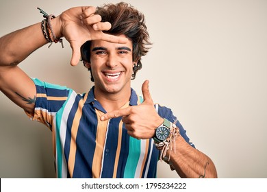 Young man on vacation wearing summer colorful shirt standing over isolated white background smiling making frame with hands and fingers with happy face. Creativity and photography concept.