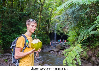 Young man on vacations in a jungle drinking coconut while hiking