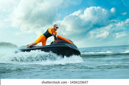 Young Man on water scooter in tropical ocean.