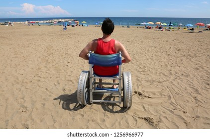 young man on wheelchair with big special aluminum wheels on the beach of tourist village in summer