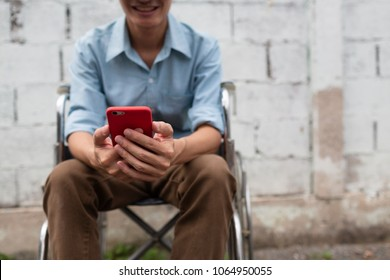Young man on wheelchair happy with mobile phone application, Disabled concept.