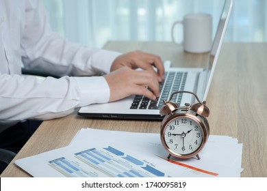 Young man on the white shirt using a laptop computer on the desk. On the desk are the alarm clock and business document.