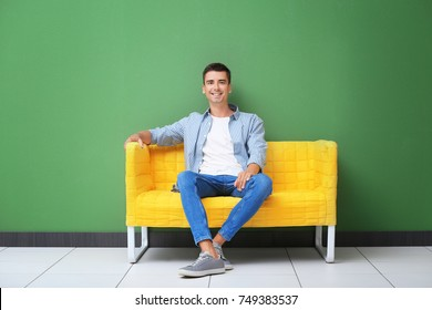 Young man on yellow sofa near color wall