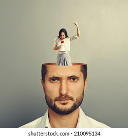 young man with open head. small angry woman standing in the man's head and screaming with megaphone. photo over grey background