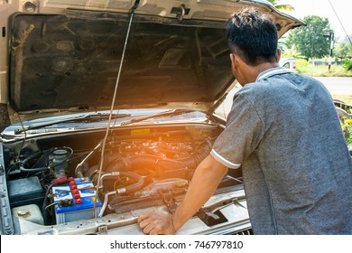 Young man opened car bonnet to see car engine over heat , broken car concept.