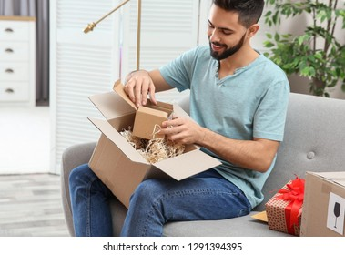 Young man opening parcel on sofa at home