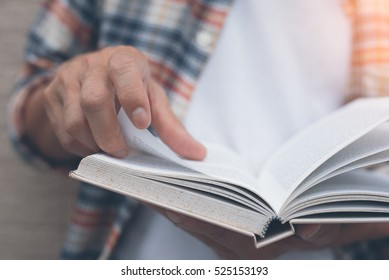 Young man opening and reading a book, close up, vintage style.