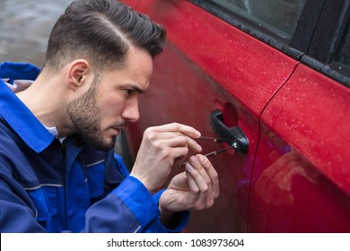 Young Man Opening Red Car Door With Lockpicker