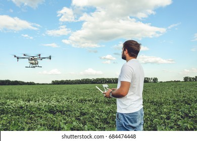 Young man operating of flying drone octocopter at the green field. Professional agriculture drone flying with blue sky.