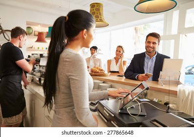 Young man ordering at the counter in a cafe