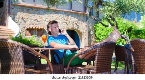 Young man in outdoor cafe talking on phone