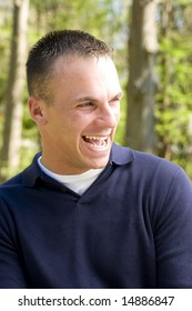 young man in outdoor setting laughing