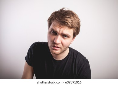 Young man with outraged face isolated on gray background. Negative human emotion facial expression feeling reaction