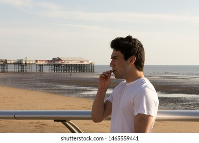 Young man outside vaping using his portable ecig device
