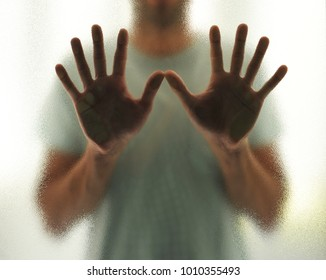 Young man with outstretched hands behind the glass, concept of isolation and loneliness